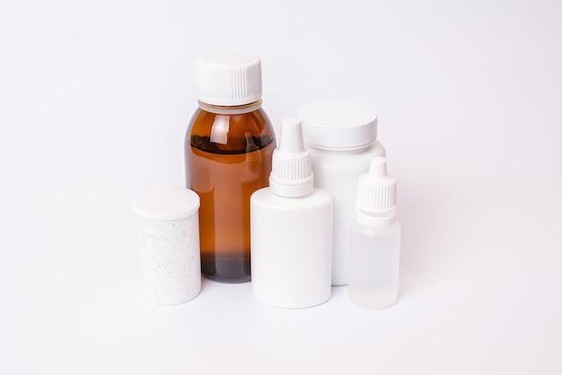 Leere leere heilmittel muster kopfschmerz medikamente nahrungsergänzungsmittel tabletten virus konzept. schließen sie herauf foto von weißen flaschen mit pille ohr augentropfen transparente braune flasche isoliert auf weißer oberfläche