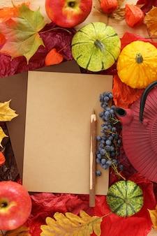 Leere leere karte mit hölzernem stift, helle blätter des ahorns, äpfel, kleine kürbise