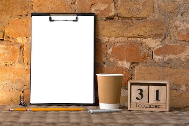 Leere leere zwischenablage auf der braunen backsteinmauer mit kaffeetasse und bleistiften. exemplar, 31. dezember, neujahrsvorsätze.