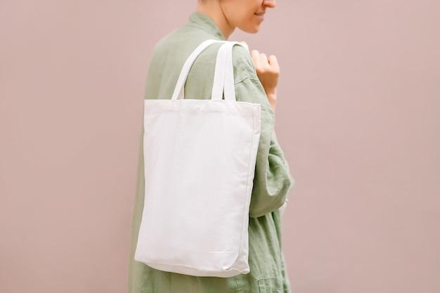 Leere leinentragetasche in den weiblichen händen. attrappe, lehrmodell, simulation. umweltfreundliches konzept.