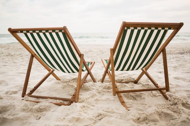 Leere liegestühle am tropischen sandstrand