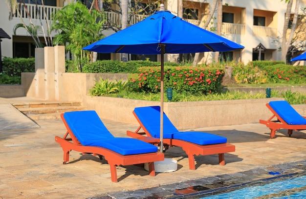 Leere liegestühle in der nähe des pools an einem sonnigen tag