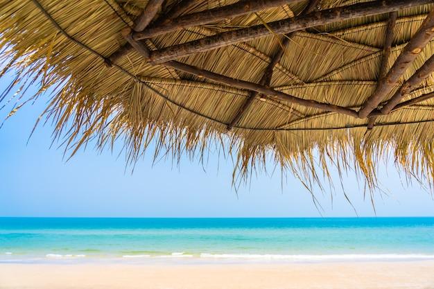 Leere liegestuhl-lounge mit sonnenschirm am strand meer ozean blauen himmel für urlaubsreise urlaub