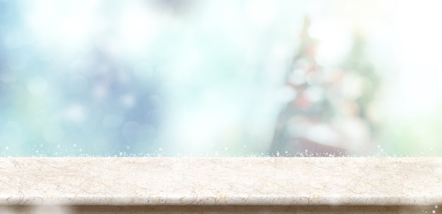 Leere marmorsteintischplatte mit abstraktem bokeh unschärfeweihnachtsbaum und schnee