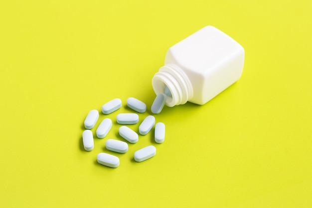 Leere medizinische flasche mit den blauen pillen, die herauskommen