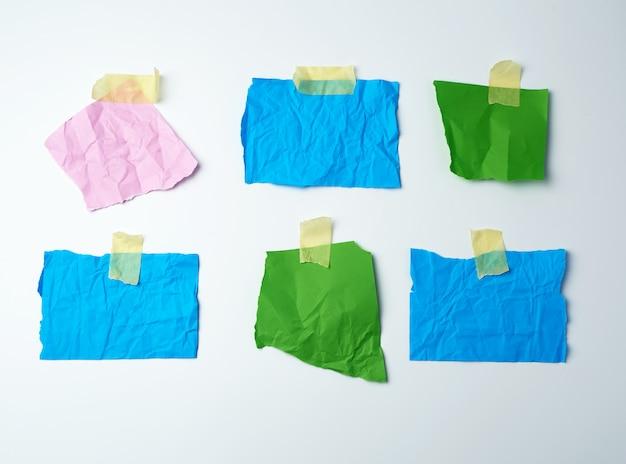 Leere mehrfarbig zerknitterte papierstücke werden mit klebeband verklebt