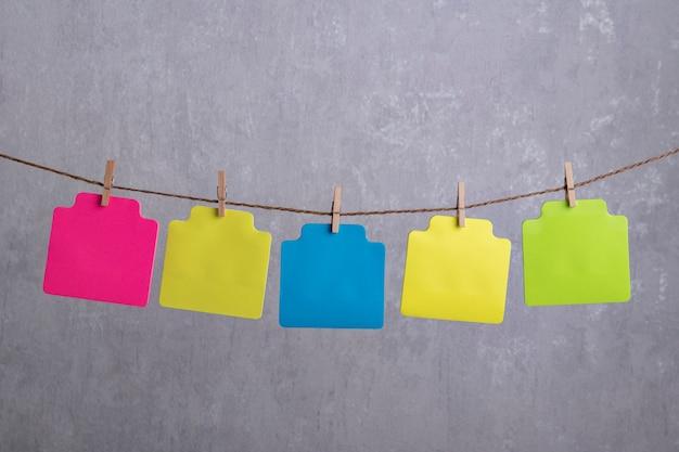 Leere mehrfarbige papierkarten hängen mit wäscheklammer am seil