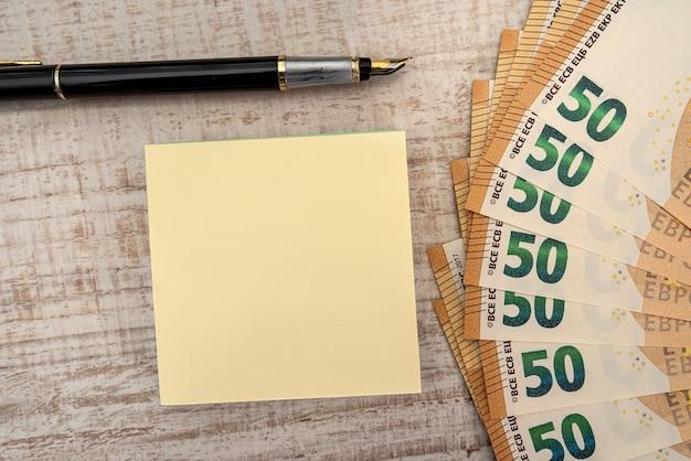 Leere memos mit stift und 50 euro banknoten. finanz- und zählkonzept