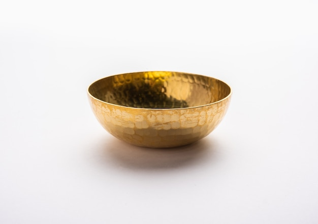 Leere messing- oder goldene metallschüssel isoliert auf weißer oberfläche