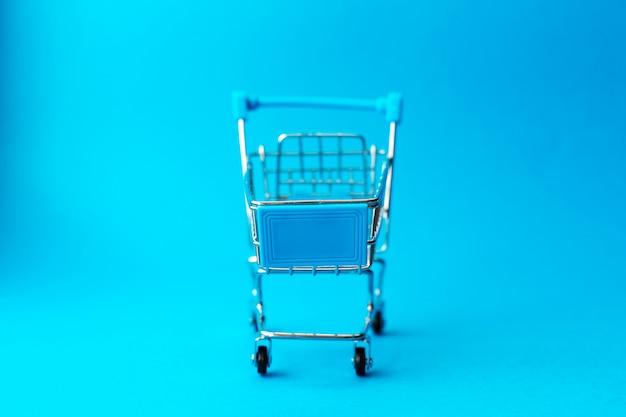 Leere metalleinkaufslaufkatze auf blauem hintergrund. rabatt und einkaufskonzept