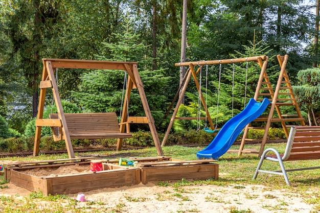 Leere moderne hölzerne kinderspielplatz gesetzt auf grünem hof im öffentlichen park im sommertag.