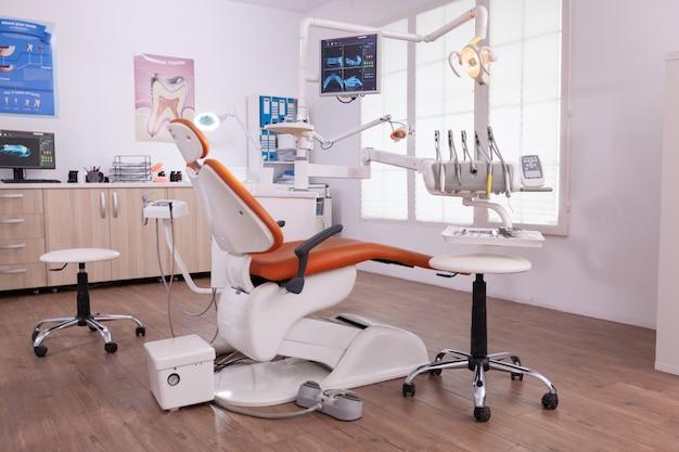 Leere moderne zahnpflege-stomatologie-krankenhausbüros mit niemandem darin, der mit zahninstrumenten ausgestattet ist, die für die kieferorthopädische gesundheitsbehandlung bereit sind. zahnröntgenbilder auf dem display