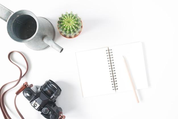 Leere notebook, bleistift, filmkamera, topf kaktus mit bewässerung, draufsicht, flache lage, isoliert auf weißem hintergrund