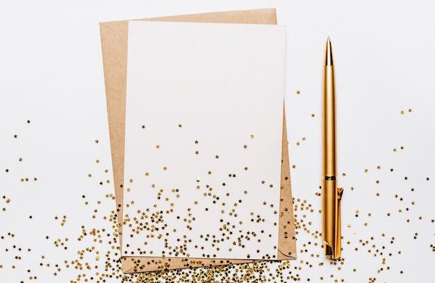 Leere notiz mit umschlag-, stift- und goldglittersternen auf weißem hintergrund