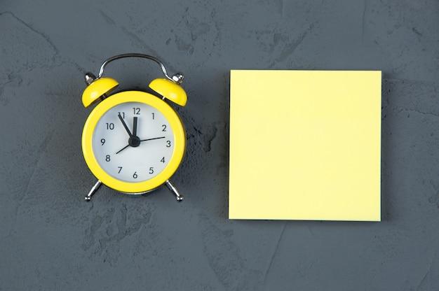 Leere notiz mit wecker auf grauem tisch, gelbe haftnotiz