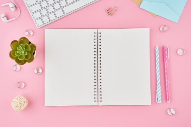 Leere notizblockseite im aufzählungszeichenjournal auf hellrosa bürodesktop. draufsicht des modernen hellen tisches mit notizbuch