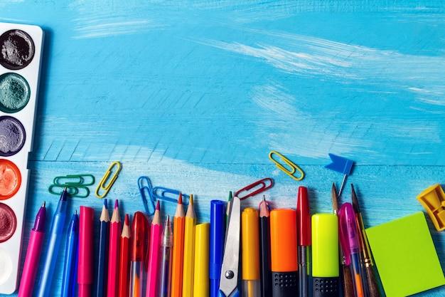 Leere notizblockseite mit stiften, markern, büroklammern, aquarellen. zurück zum schulkonzept.
