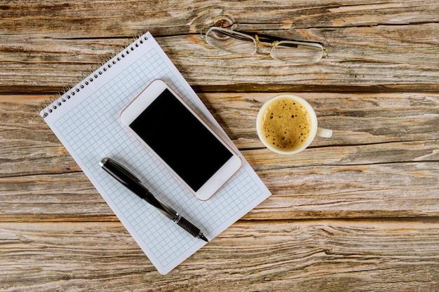 Leere notizbuch- und smartphone-bleistift-tasse kaffee auf holztisch