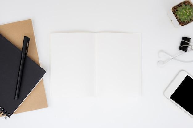 Leere notizbuchseite auf weiße schreibtischtabelle. draufsicht, flach zu legen.