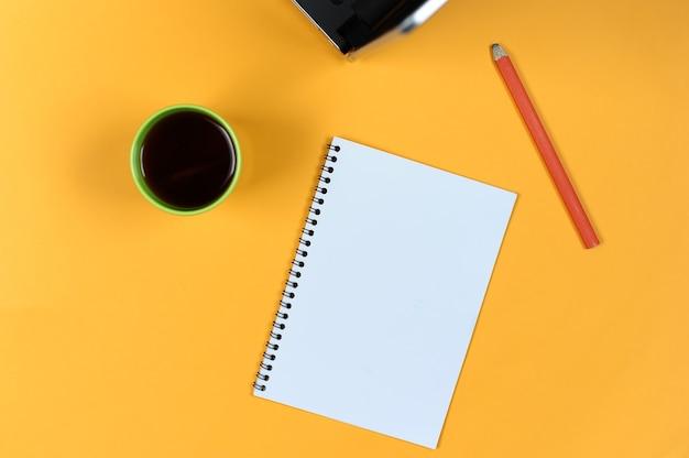 Leere notizbuchseite, laptop, kaffeetasse und bleistift. leerer schreibblock für ideen und inspiration auf farbigem hintergrund