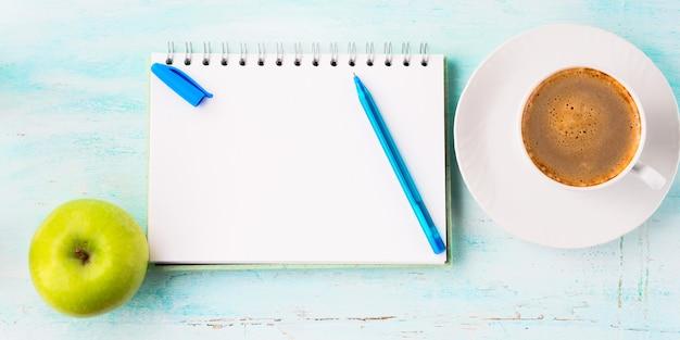 Leere notizbuchseite mit blauem stift und schalenkaffee blüht