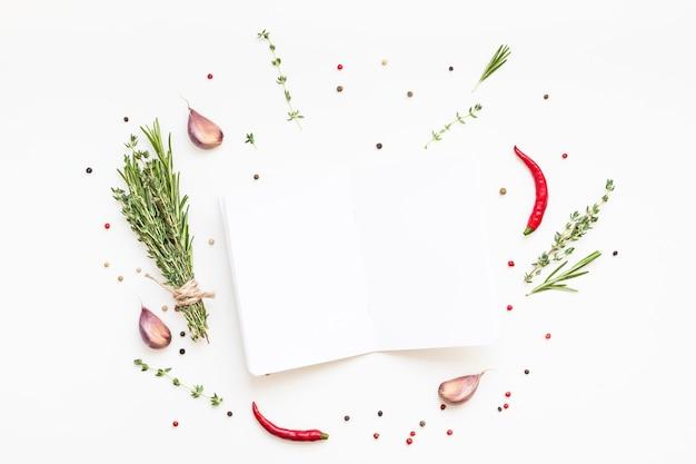 Leere notizbuchseiten auf weißer oberfläche mit grünen kräutern und gewürzen