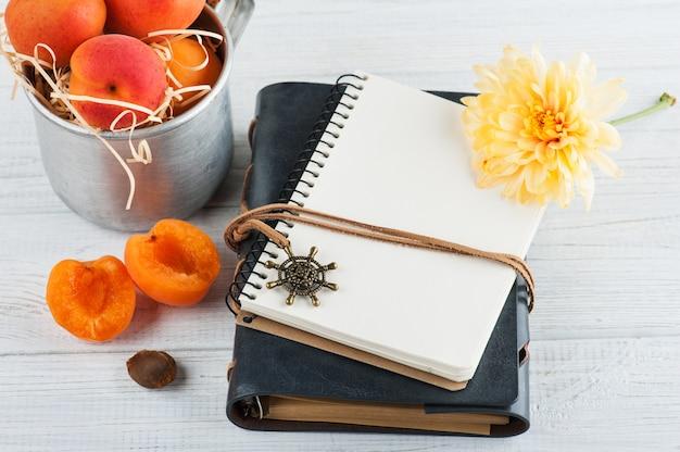 Leere notizbücher, aprikosen im zinnbecher, blume