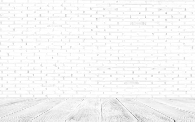 Leere oberseite des holztischs auf weißem ziegelsteinhintergrund. zur präsentation oder montage ihrer produkte