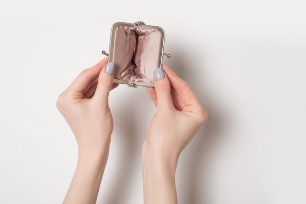Leere offene metallgeldbörse in den weiblichen händen