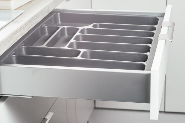 Leere offene schublade aus weißem küchenset mit schwarzem besteck-organizer-tablett, seitenansicht. küchenaufbewahrungssystem