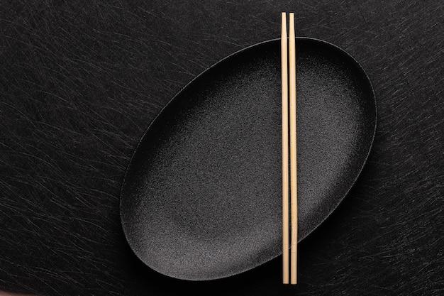 Leere ovale schwarze platte mit essstäbchen auf dunklem hintergrund im japanischen essensstil draufsicht flach