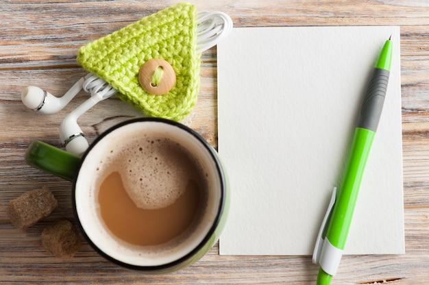 Leere papieranmerkung, grüner stift, kopfhörer und tasse kaffee