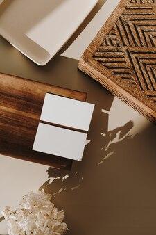 Leere papierblattkarten, holztablett, sarg und trockene blumen mit sonnenlichtschatten auf beige