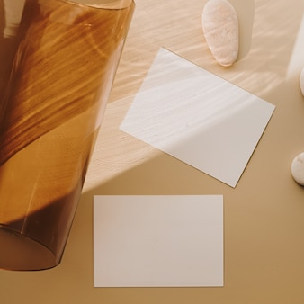 Leere papierblattkarten mit hellbrauner glasröhre mit sonnenlichtschatten auf weiß