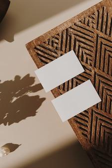 Leere papierblattkarten mit hölzernem sarg und sonnenblumenschatten der trockenen blumen auf beige