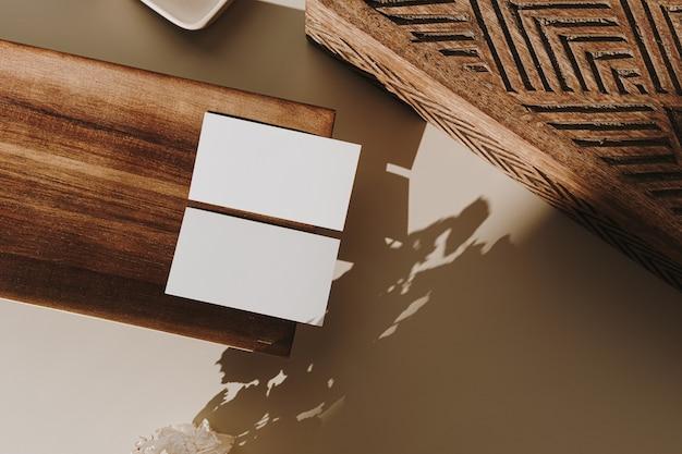 Leere papierblattkarten mit kopierraum, holztablett, sarg und trockenen blumen mit sonnenlichtschatten auf beige