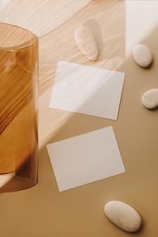 Leere papierblattkarten mit leerem kopierraum und hellbrauner glasröhre mit sonnenlichtschatten auf weiß