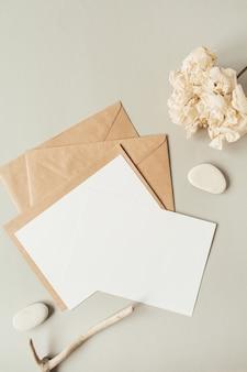 Leere papierbögen mit leerem kopierraum für text, umschläge, hortensienblume, steine auf beige