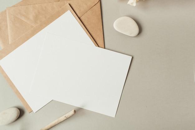 Leere papierbögen mit leerem kopierraum für text, umschläge, hortensienblume, steine auf beiger oberfläche