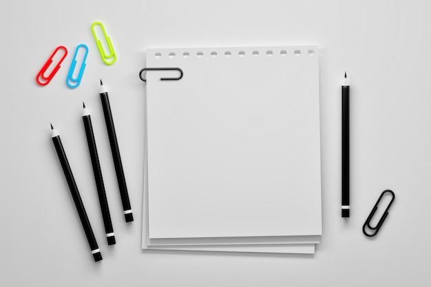 Leere papierbögen mit stiften und büroklammern
