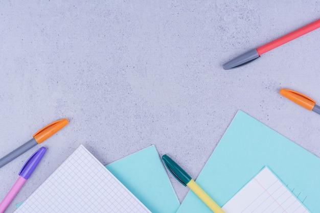 Leere papiere und buntstifte auf grau.