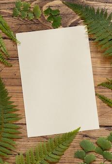 Leere papierkarte auf einem mit farnblättern verzierten holztisch draufsicht. tropische mock-up-szene mit flacher einladungskarte