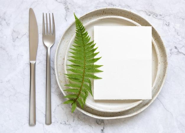 Leere papierkarte beim auflegen auf einen teller auf marmortisch mit farnblättern um die draufsicht. tropische mock-up-szene mit flacher einladungskarte