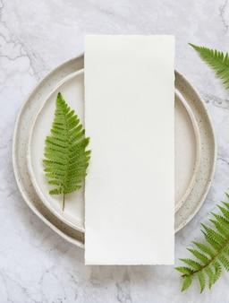 Leere papierkarte beim auflegen auf einen teller auf marmortisch mit farnblättern um die draufsicht. tropische mock-up-szene mit flacher menükarte