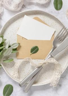Leere papierkarte im umschlag auf weißem teller mit gabel und messer auf marmortisch mit eukalyptuszweigen und vintage-bändern herum, draufsicht. kartenmodell