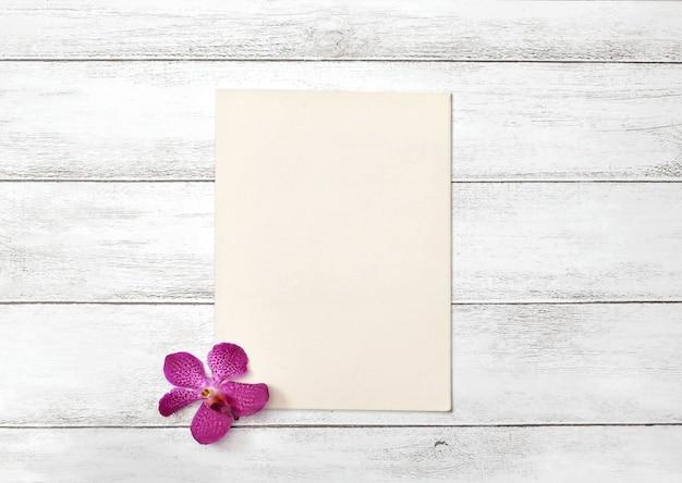 Leere papierkarte mit frühlingsorchideenblume auf weißem holz