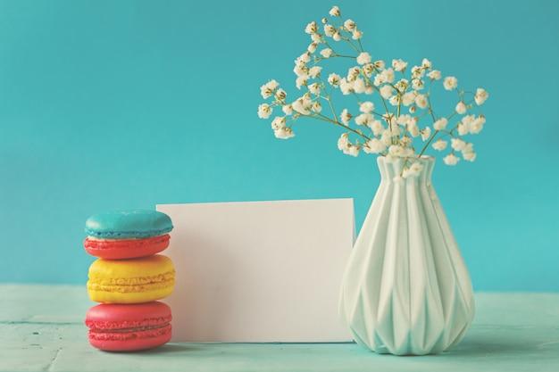 Leere papierkarte mit tasse tee und vase in blume und makronen für frauentag