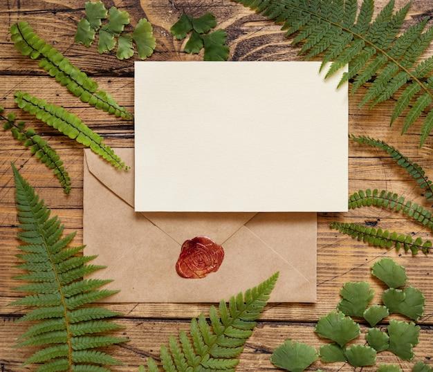 Leere papierkarte mit versiegeltem umschlag und rotem wachssiegel auf braunem holztisch mit farnblättern um die draufsicht. tropische mock-up-szene mit flacher einladungskarte