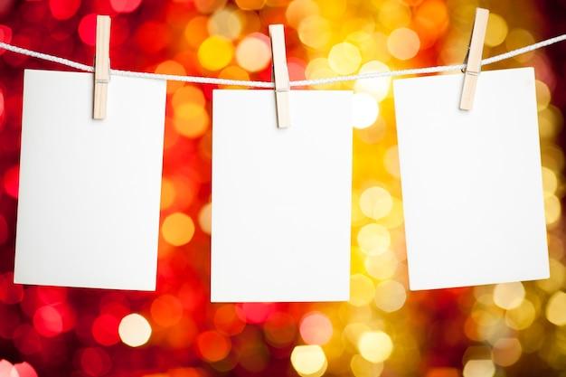 Leere papierkarten hängen an wäscheklammern vor weihnachtsbeleuchtung hintergrund