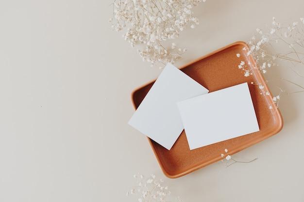 Leere papierkarten mit kopierraum auf teller und gypsophila-blumen auf beige. flache lage, draufsicht.